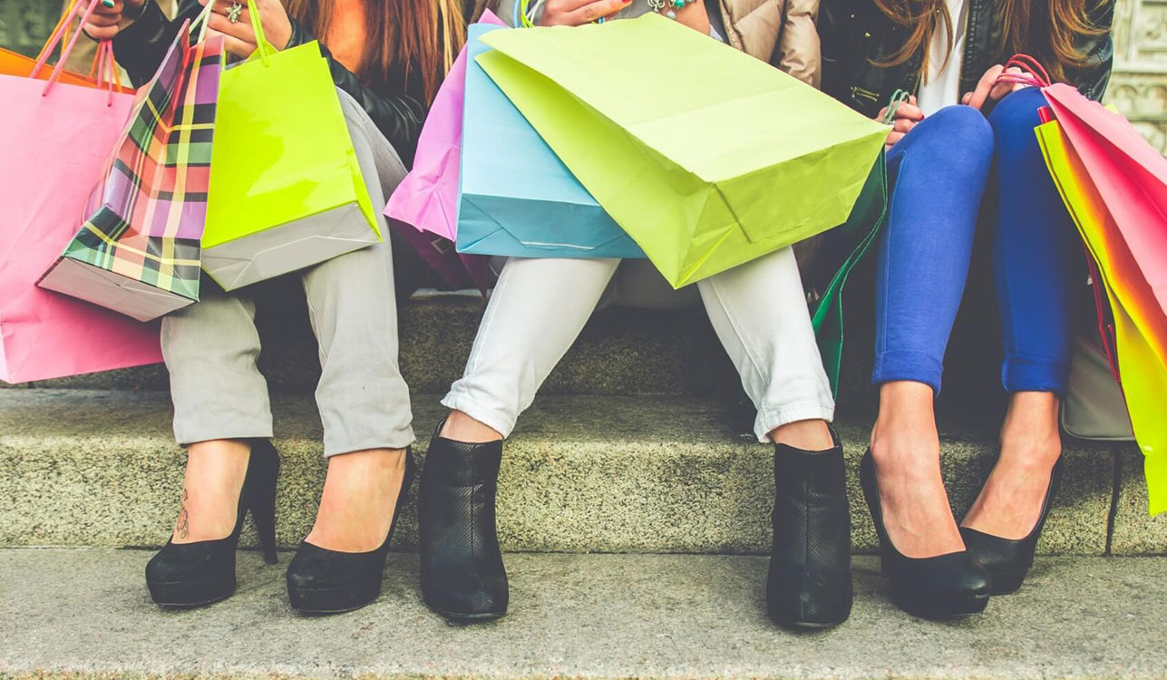 Women Sitting With Shopping Bags